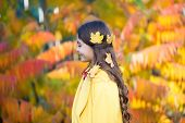Creative Way To Use Those Autumn Leaves. Small Girl Wearing Autumn Leaves In Long Brunette Hair. Aut poster