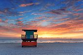image of lifeguard  - Miami South Beach sunrise with lifeguard tower and coastline with colorful cloud and blue sky - JPG