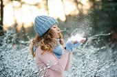 Beauty Winter Girl Blowing Snow In Frosty Winter Park. Outdoors. Flying Snowflakes. Sunny Day. Joyfu poster