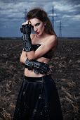 Informal Fashion: The Pretty Fit Young Gothic Girl Dressed In Black Leather Skirt And Gloves. Outdoo poster