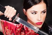 stock photo of sword  - Close up of a pretty woman and katana - JPG