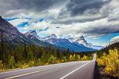 The highway crosses the Rocky Mountains of Canada. Magnificent northern autumn. Canadian Rockies. Th poster