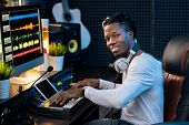 Happy young musician with headphones on neck looking at you while working over new music by workplac poster