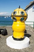 stock photo of plinth  - An antique diving bell painted yellow with viewing portals on a white plinth at a quay with the sea in the background - JPG
