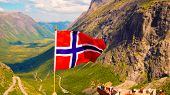 Trollstigen Mountain Road Landscape In Norway, Europe. Norwegian Flag Waving And Many Tourists Peopl poster