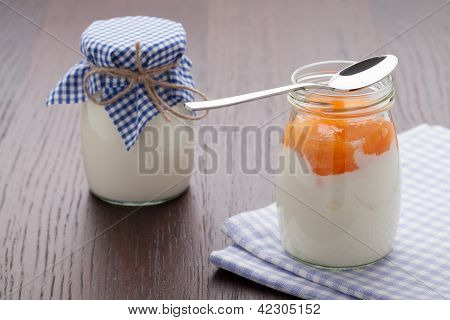 Homemade Milk Yogurt With Fruit Jam In Glass Pot On Table