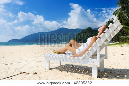 Girl on a tropical beach sitting at chaise lounge