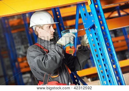 One warehouse worker in uniform with power tool drilling hole during rack arrangement erection work