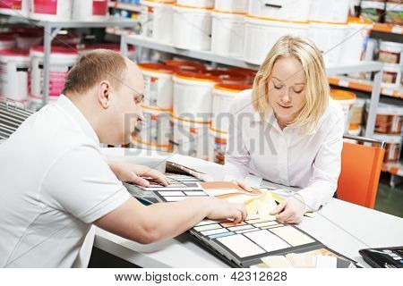 Assistant seller help choosing paint color and demonstrating matching samples to buyer at hardware store