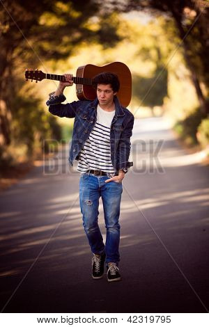 drifter, man with guitar walking outdoors