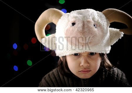 Portrait of authentic angry kid wearing funny sheep hat