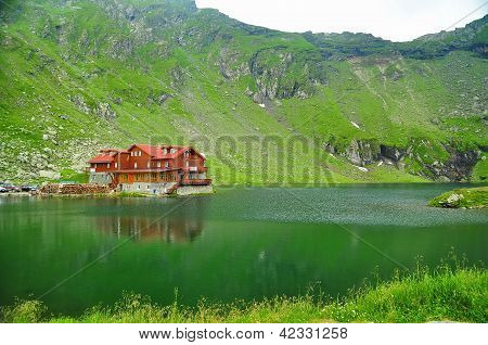 Brown Wooden House On Glacier Lake With Very Clear Mountain Water, Balea Lac, Romania