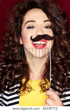 Attractive playful young woman holding mustache on a stick