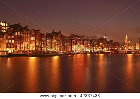Night in Amsterdam at the river Amstel with the Munt tower in the Netherlands