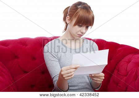 Young Beautiful Red Haired Girl Get Bad News On Red Sofa In Front Of White Background