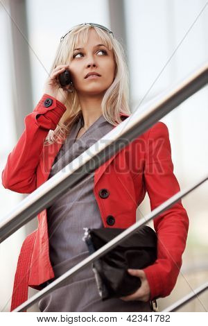 Young businesswoman calling on the phone against office windows