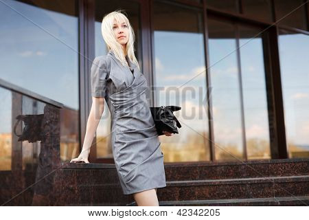 Young businesswoman on the steps against office windows