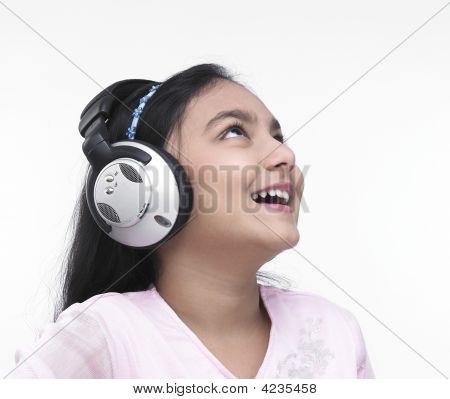 An Asian Teenage Girl Of Indian Origin Listening To Music