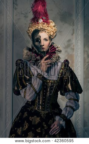 Haughty queen in royal dress with mask