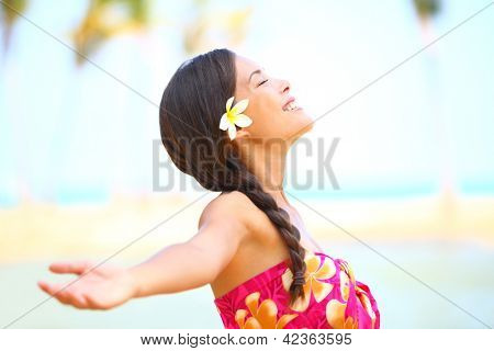 Freedom beach woman smiling happy and serene with arms outstretched in free pose. Beautiful spiritual elated happiness concept image with multicultural Asian / Caucasian female model.
