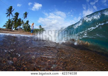 Young lady standing on a tropical beach with dark volcanic sand and watching barrel waves. Dauin, Negros oriental, Philippines