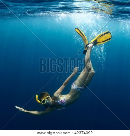 Underwater shoot of a young lady diving on a breath hold in a clear sea with sunbeams shining through the water