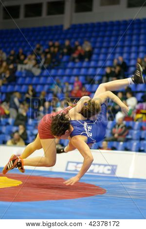 KIEV, UKRAINE - FEBRUARY 16: Match between Omelchenko, Ukraine, red and Martinakova, Czech Republic during International female wrestling tournament in Kiev, Ukraine on February 16, 2013. Motion blur