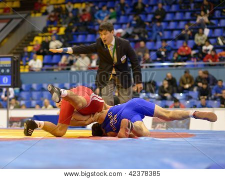 KIEV, UKRAINE - FEBRUARY 16: Match between Rudenko, Ukraine, blue and Jaburyan, Armenia during International freestyle wrestling and female wrestling tournament in Kiev, Ukraine on February 16, 2013