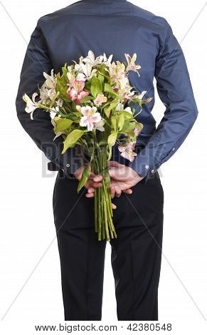 Man hold bouquet bouquet of flowers behind his back.  isolated o