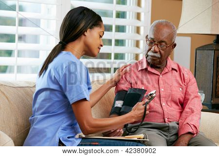 Nurse Visiting Senior Male Patient At Home