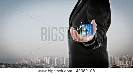 Hombre de negocios mantener elementos de energías alternativas (célula solar, tierra, turbina de viento) de este furni de imagen
