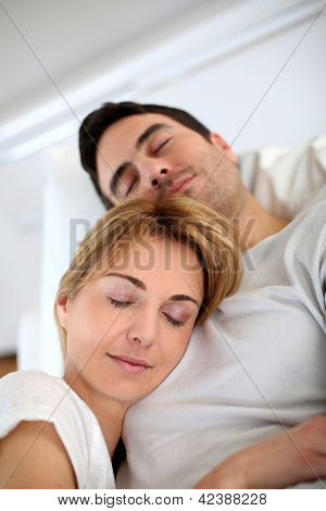 Couple taking a nap in sofa at home
