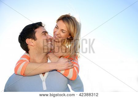 Man giving piggyback ride to girlfriend by the sea
