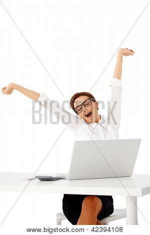 Attractive young busineswoman in glasses sitting behind a table stretching her arms into the air and yawning