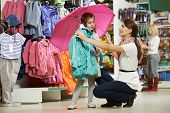 stock photo of outerwear  - woman and little girl choosing and trying on raincoat during shopping at outerwear supermarket - JPG