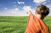 stock photo of float-plane  - young boy flying a paper airplane on a summers day - JPG