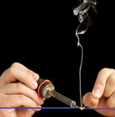 image of flux  - Soldering Tech soldering a blue wire on a pure black background - JPG
