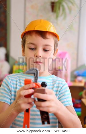 Boy In Plastic Helmet With Toy Tools