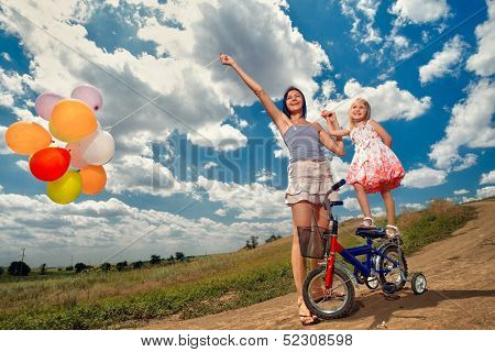 View of happy mother with little girl playing with balloons