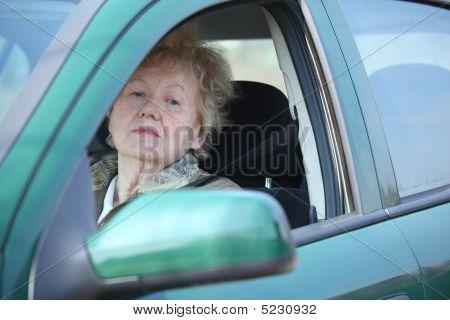 Elderly Woman Looks In Car`s Window