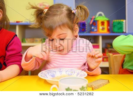 Little Girl Eats In Kindergarten