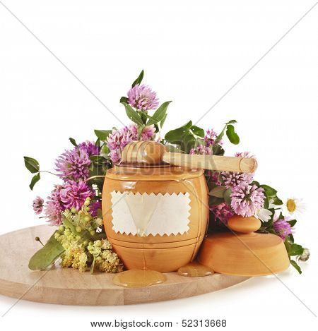 sweet honey in  barrel pot and wooden drizzler in wood board, isolated on white background