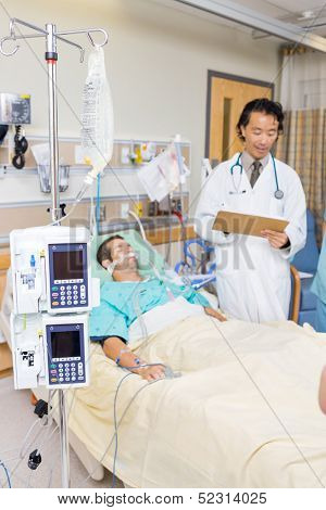 Dialysis machine and infusion bottle with doctor examining patient's report in hospital