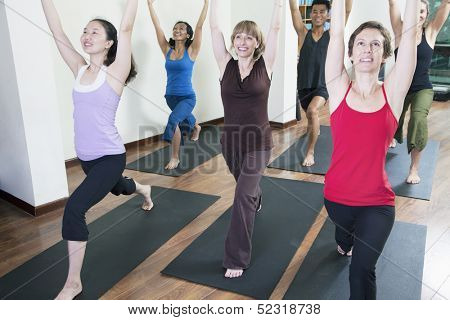 Group of people with hands raised doing yoga during a yoga class