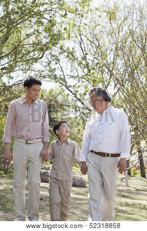 Multi-generational family holding hands and walking