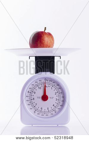 Red Apple On Kitchen Weighing Scales On White Background