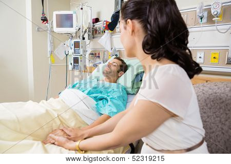 Young woman holding man's hand lying on bed in hospital