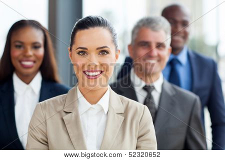 cute businesswoman standing with co-workers in office