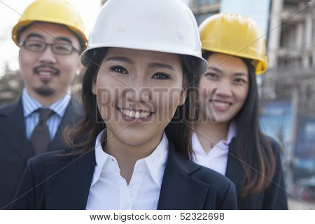 Portrait of three architects wearing hardhats
