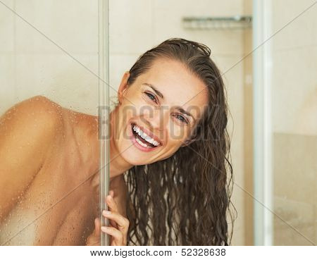 Smiling Young Woman Looking Out From Shower Cabin